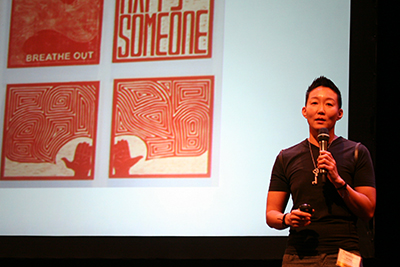 YK speaking into a mic and standing in front of screen with YK's artwork